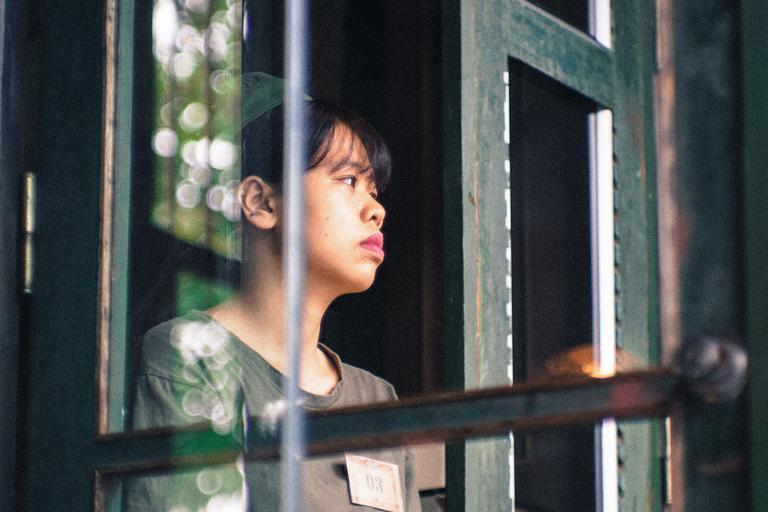 Muž stojí pri otvorených sklenených dverách