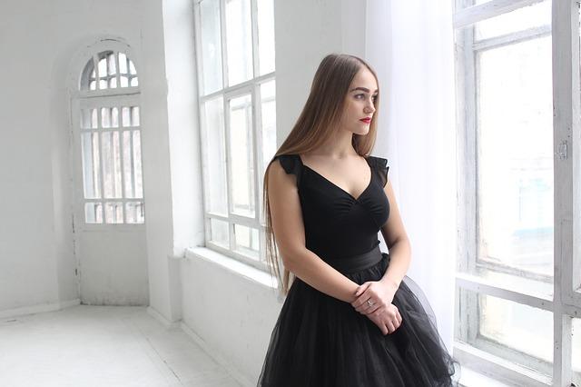 Žena v čiernych šatách stojí pri okne a pozerá sa von.jpg