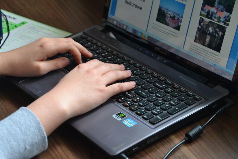 Práca s notebookom, prsty na klávesnici