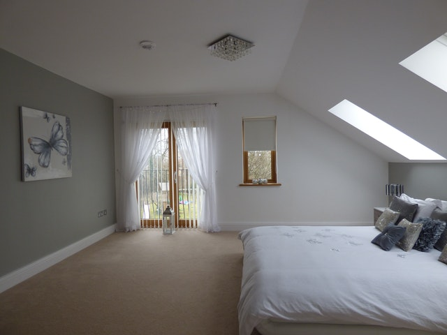 Spálňa v podkroví s dvoma oknami a balkónovými dverami