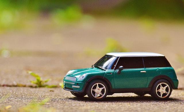 Zelené auto na betóne medzi rastlinkami
