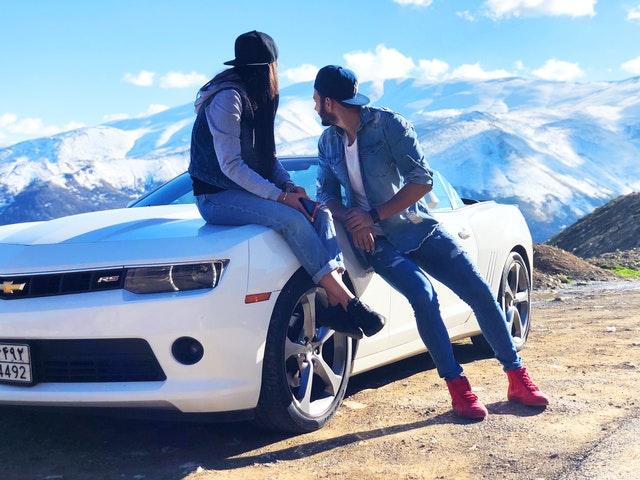 Dievča a chlapec sa opierajú o biele auto
